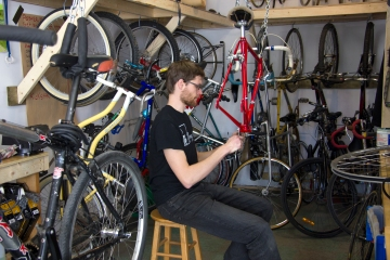 Pal fixes a bike at Long Alley Bicycles.